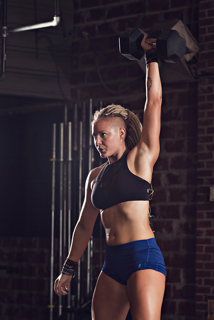fit woman performing dumbbell snatch
