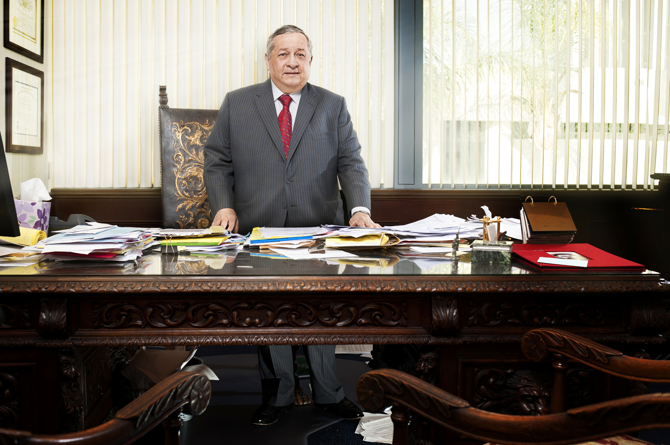Man standing at a really cluttered desk.  Kenneth M. Ruggiano is a photographer in Tulsa Oklahoma