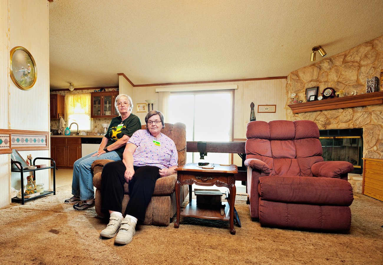 Two women sitting in the living room of their double wide.  Kenneth M. Ruggiano Photographer based in Tulsa Oklahoma