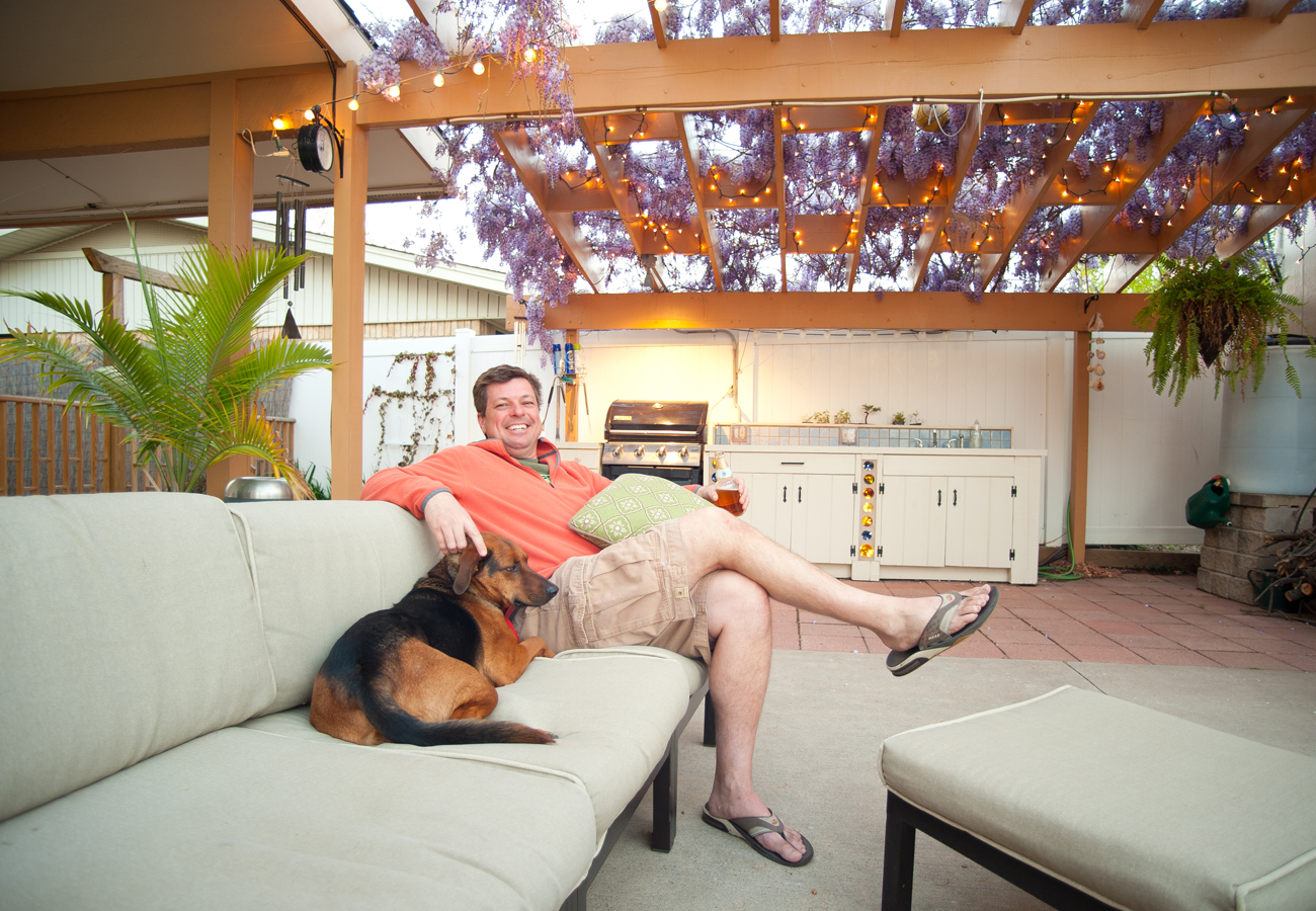 Man sitting with his dog in his backyard oasis.  Kenneth M. Ruggiano Photographer based in Tulsa Oklahoma