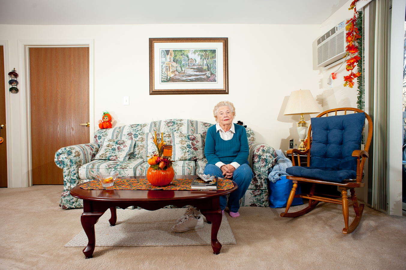 Grandmother sits awkwardly in her living room.  Kenneth M. Ruggiano Photographer based in Tulsa Oklahoma