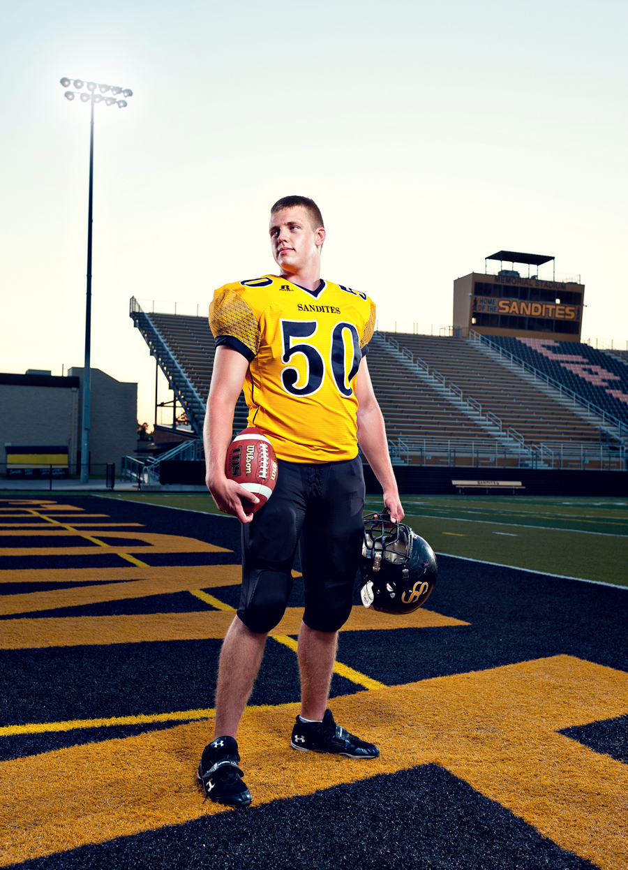 High school football player poses regally on his school's field.   Kenneth M. Ruggiano is a portrait photographer living in Tulsa, Oklahoma specializing in Sports and Athletic Photography.