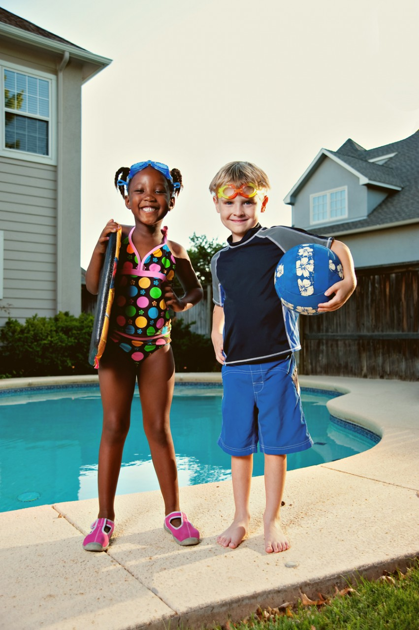 Two children posing in front of a home pool as they get ready to play.  Kenneth M. Ruggiano is a portrait photographer living in Tulsa, Oklahoma specializing in Sports and Athletic Photography.