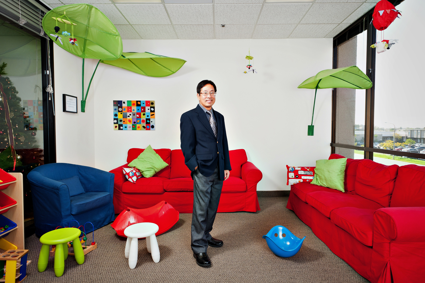 Asian Pediatric Doctor poses in suit and tie in waiting room of his practice.  Kenneth M. Ruggiano Tulsa Oklahoma based Photographer