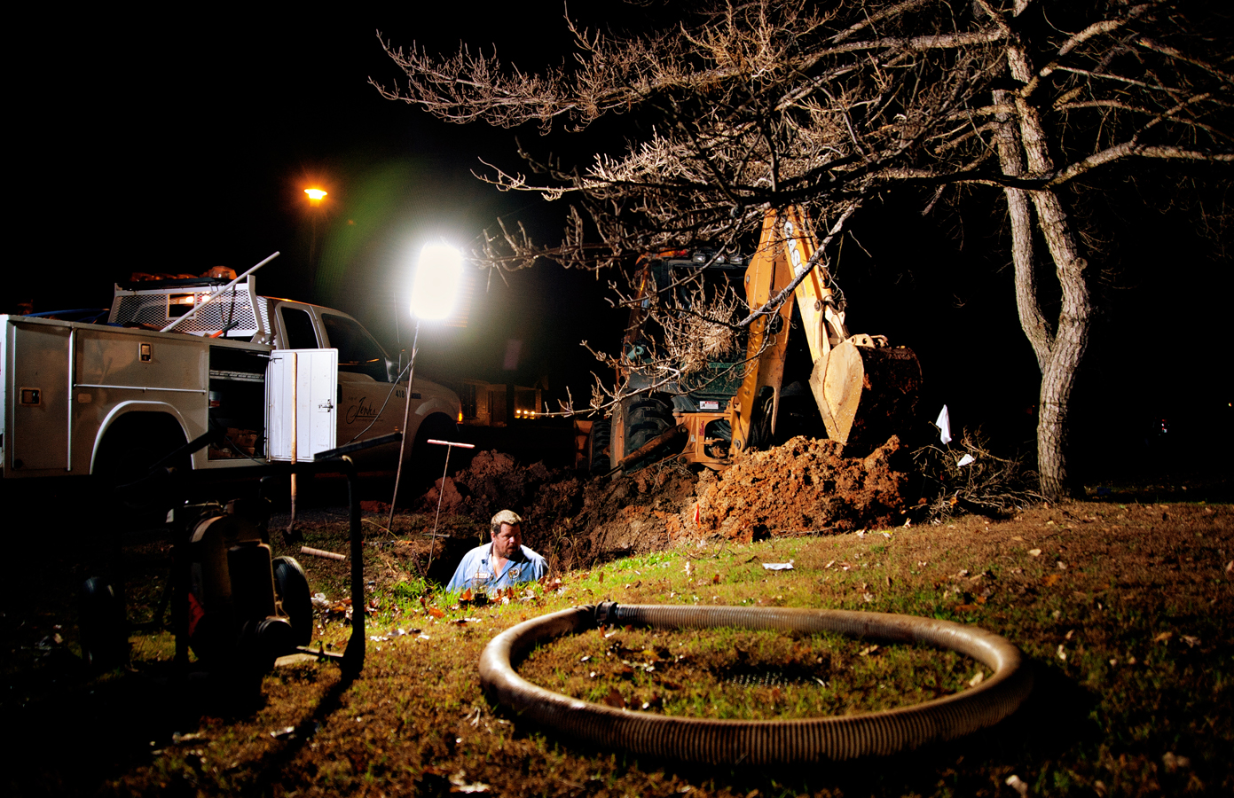 Man working on a water line break standing in the whole he has dug.  Kenneth M. Ruggiano is a Editorial Photographer based in Tulsa, Ok