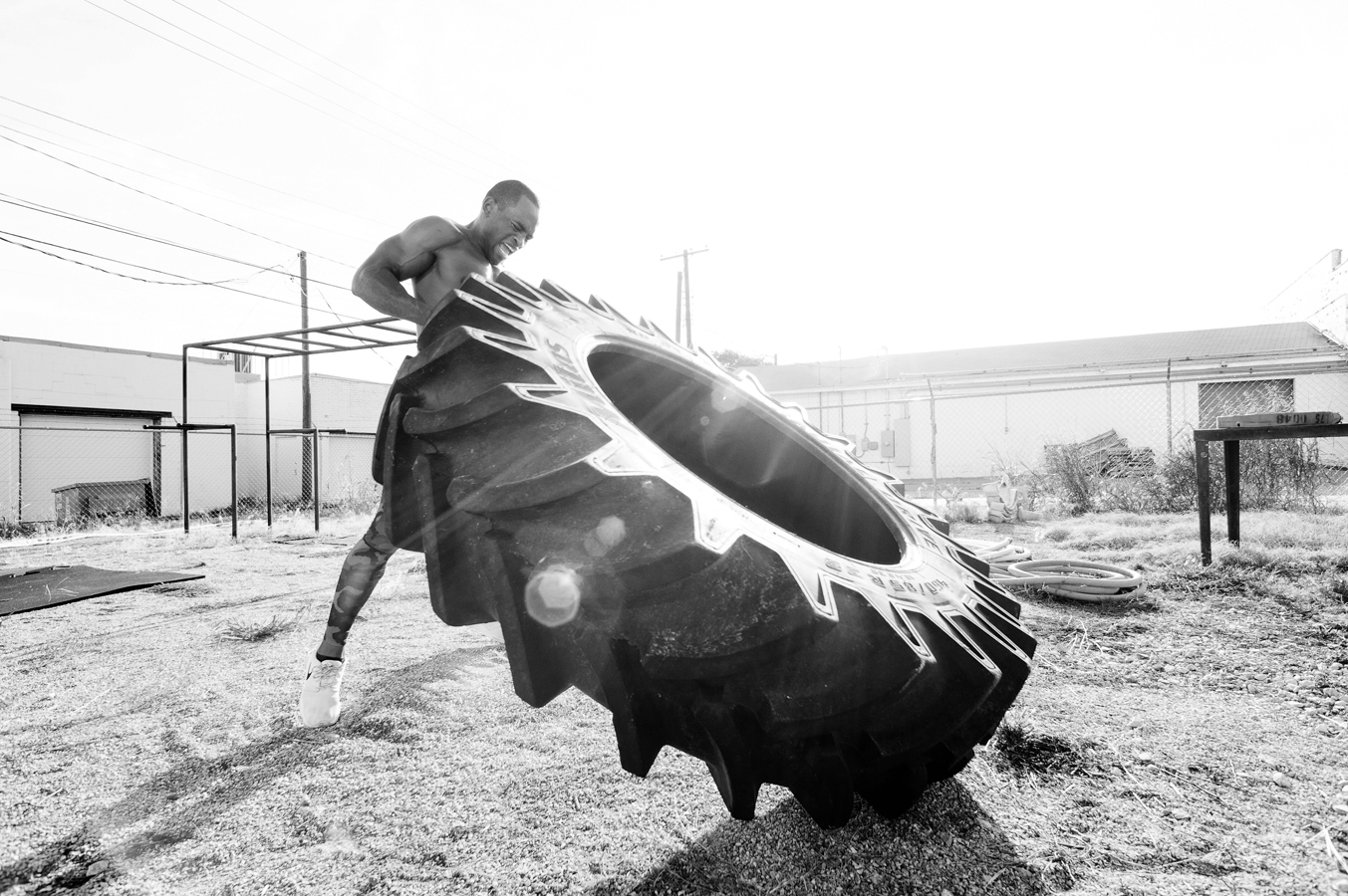 Fit black man working out outside shirtless flipping tires.   Kenneth M. Ruggiano is a photographer specializing in Sports and Fitness Photography based in Tulsa Oklahoma.