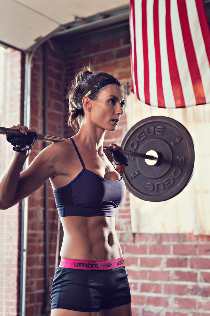 Fit women working out with a bar bell.  The American flag in the background makes this photo extra Patriotic.   Kenneth  M. Ruggiano is a sports and fitness photographer based in Tulsa Oklahoma.